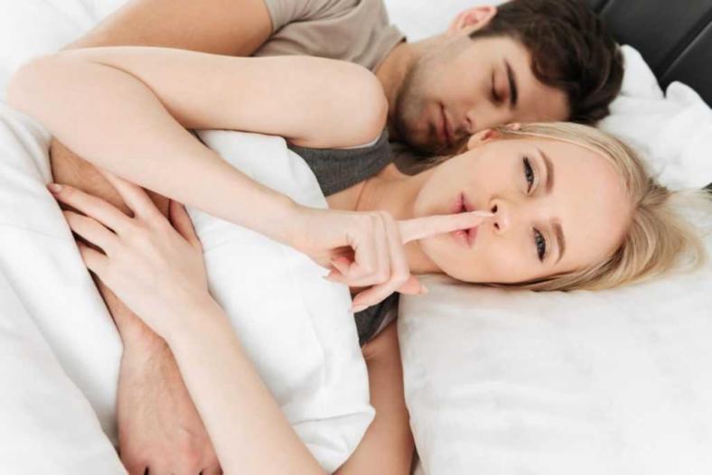 Kobieta i mężczyzna leżący w łóżku. Kobieta palcem wskazującym sygnalizuje ciszę dotykając swoich ust.