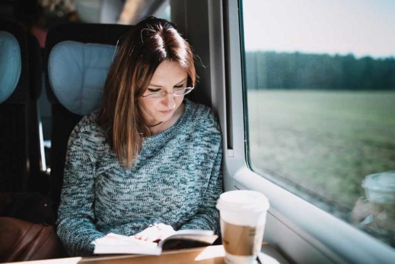 Kobieta siedząca w pociągu przy oknie czytająca książkę